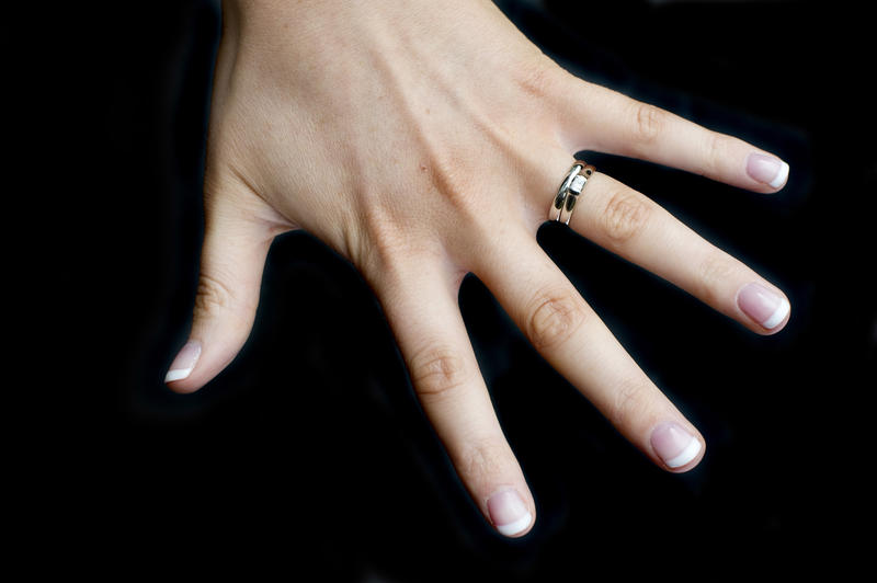 a caucasian female hand on a black background wearing wedding and engagement rings