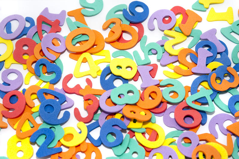 A colourful educational background with scattered numerals on a white surface, conceptual of learning numbers