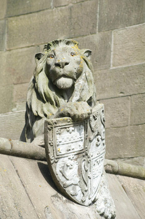 The stone sculpture of the lion with its heraldic shield on the Gothic revival Cardiff Castle Animal Wall at Cardiff Castle in Wales