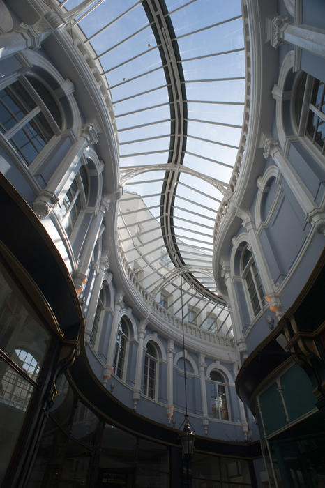 Curving glass roof and arched Venetian windows of the Morgan Arcade, a restored Victorian shopping arcade in Cardiff, Wales