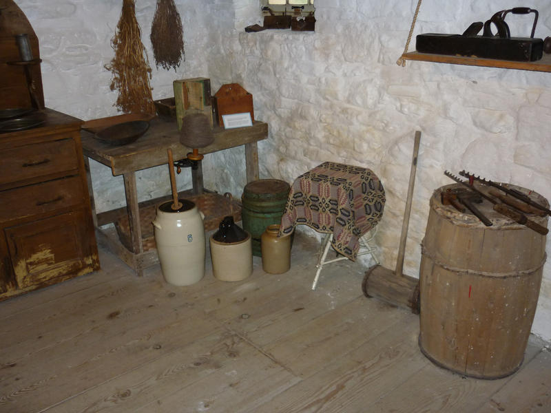 Interior of a vintage simple country kitchen with rudimentary furniture and implements and ceramic storage jars