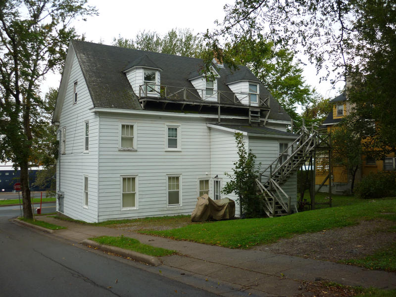 Old traditional wooden white painted house with dormer windows in Sydney, Nova Scotia