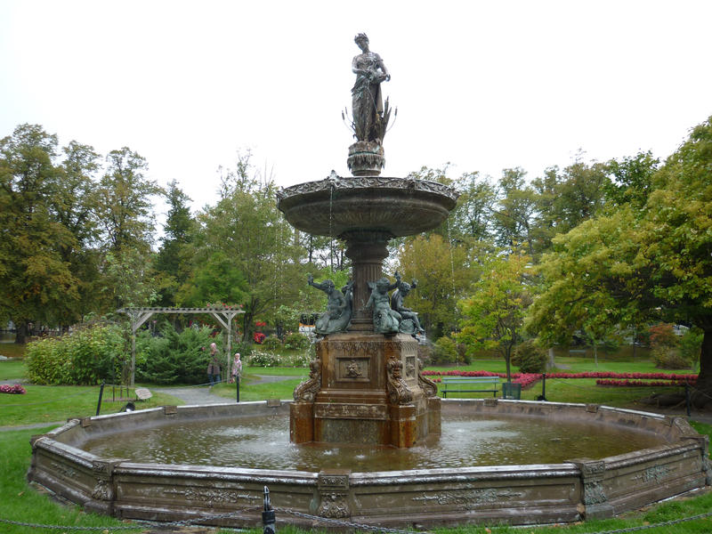 Beautiful figural fountain of a maiden pouring water in a formal leafy green garden in a park