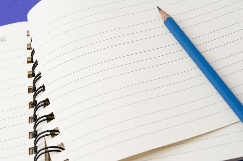 Pencil lying on a blank notebook ready for your note or message to be written