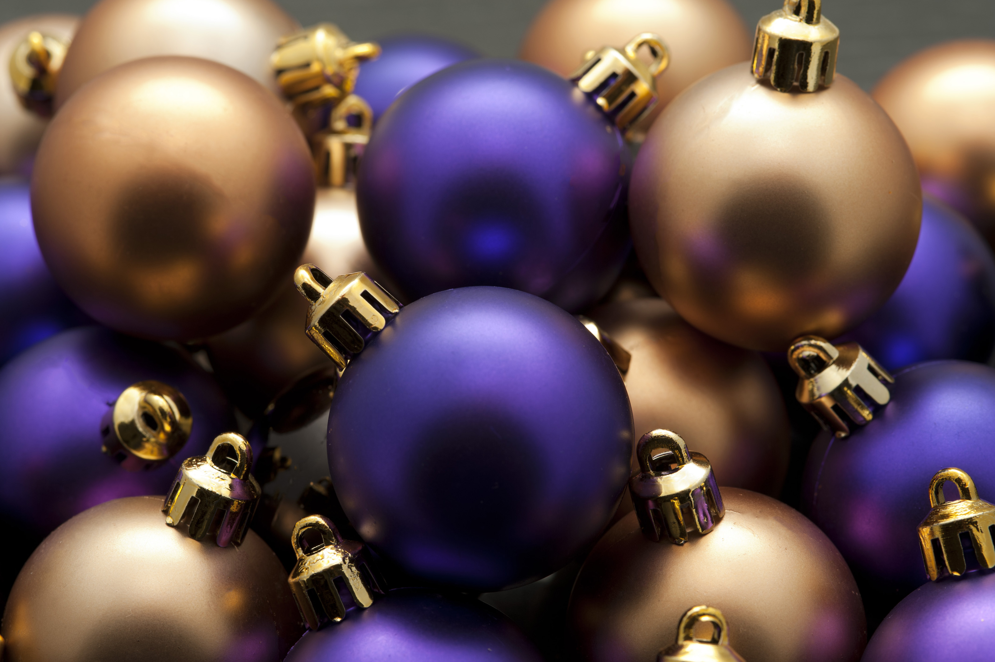 closeup background of round shiny purple and gold christmas baubles in a random pattern