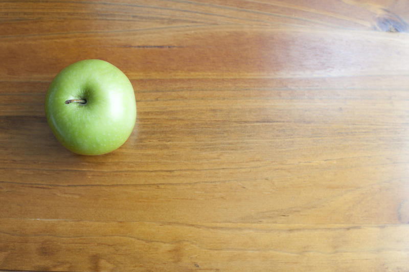 A single green apple on a wooden school desk background, with space for your text