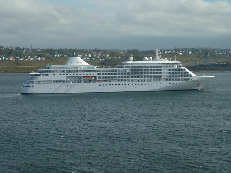 Silversea passenger cruise liner sailing along parallel to urban coastline during one of its vacation voyages