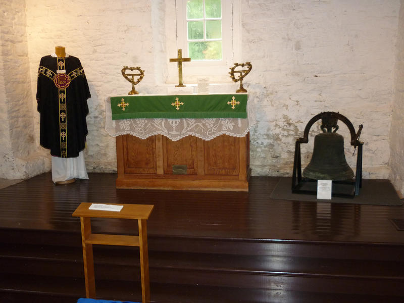 Small simple altar in a rustic church or chapel with a priests robes and bronze bell on display flanking the altar