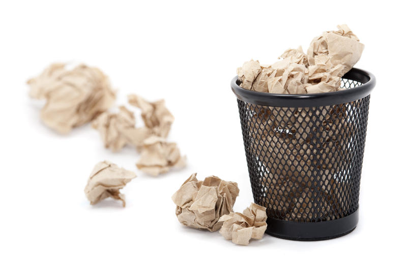 Wastepaper basket filled with crumpled paper which is overflowing onto the floor alongside it