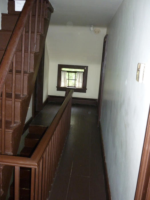 Wooden staircase and floorboard landing in an old, empty house, looking towards small window