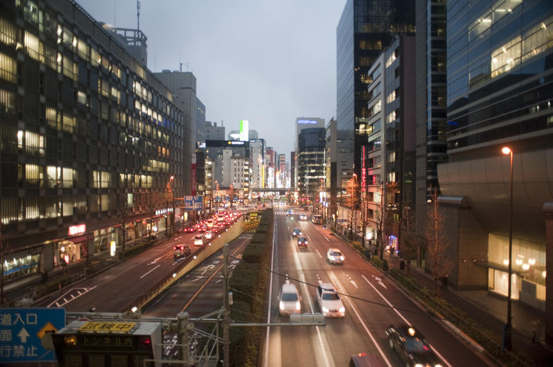 traffic and bright neon signs, evening in downtown Tokyo, Japan