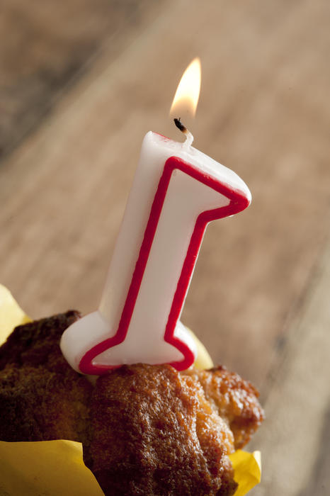 First anniversary celebration concept with a burning number one candle on a freshly baked muffin, close up high angle view