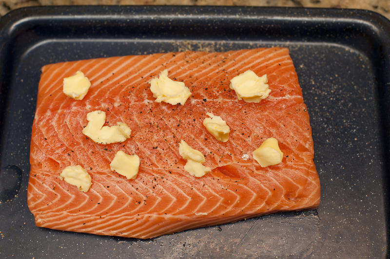 Close up Slice of Baked Salmon with Butter on Top for Dinner Served on a Black Tray