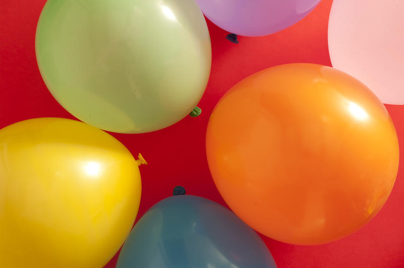 Full frame overhead background of colorful party balloons on red for a festive theme