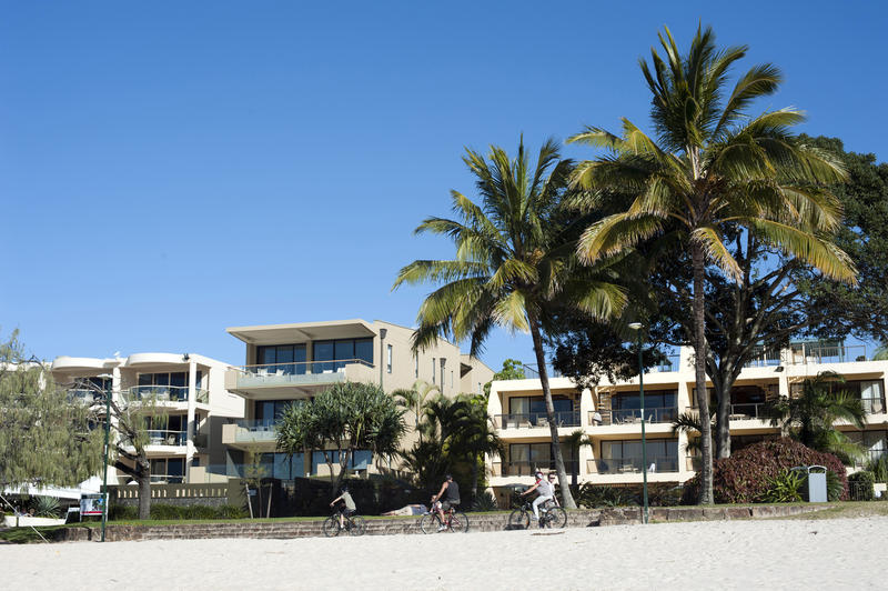 Modern tropical beachfront hotel with people riding bicycles in the foreground and palm trees against a sunny blue summer sky