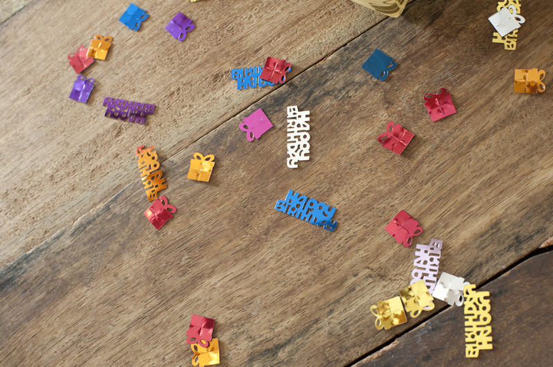 Colorful Birthday sprinkles or confetti with Happy Birthday text or multicolored gifts shapes tied with ribbon scattered randomly on a wooden table with copyspace for your greeting