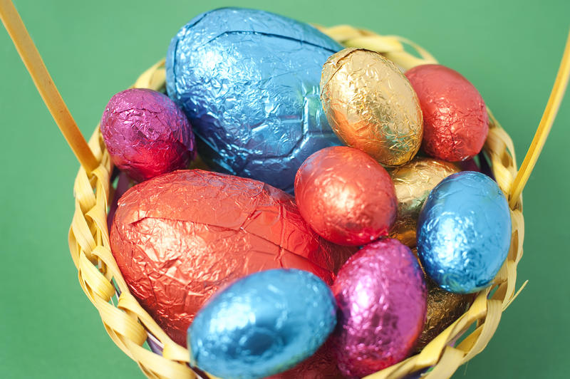 Overhead view of a basket filled with brightly coloured Easter Eggs in various sizes