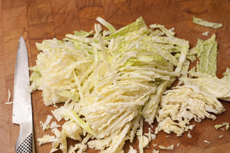 Finely chopped cabbage on a kitchen counter ready to be cooked as a vegetable accompaniment or turned into a cole slaw salad