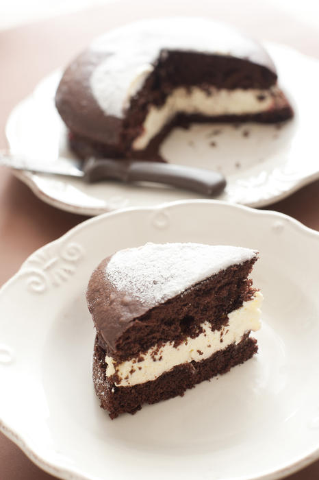 Slice of delicious freshly baked chocolate cake filled with cream or buttercream and served on a plate for dessert