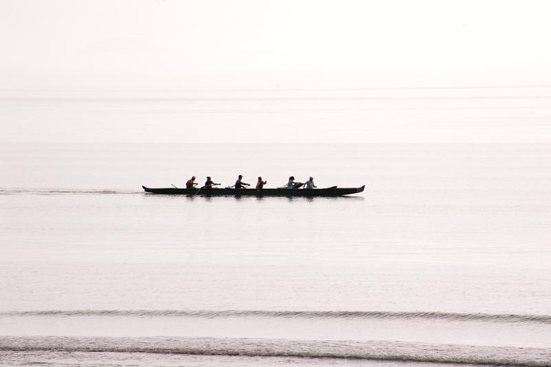 Silhouette of a team of rowers in a canoe practicing and training for a race on bright calm water