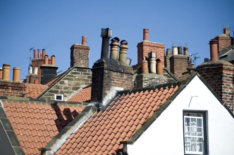 View across typical English cottage rooftops with a variety of chimneys and chimney pots under a blue sky