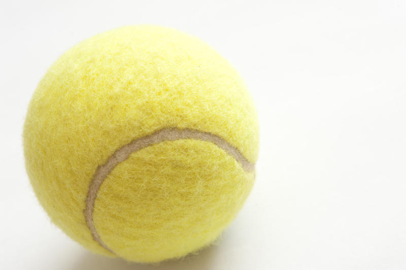 Close up of a yellow tennis ball on white with copyspace in a sport and fitness concept