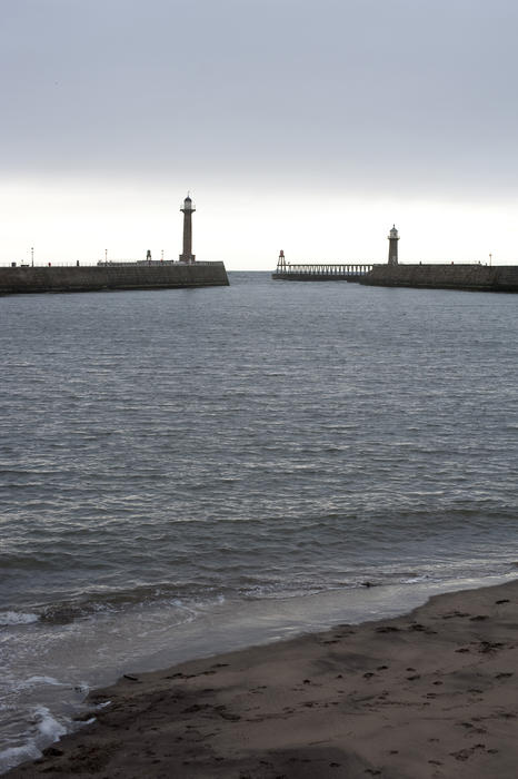 View across the calm water of Whitby harbour to the entrance with its navigation lights and stone piers