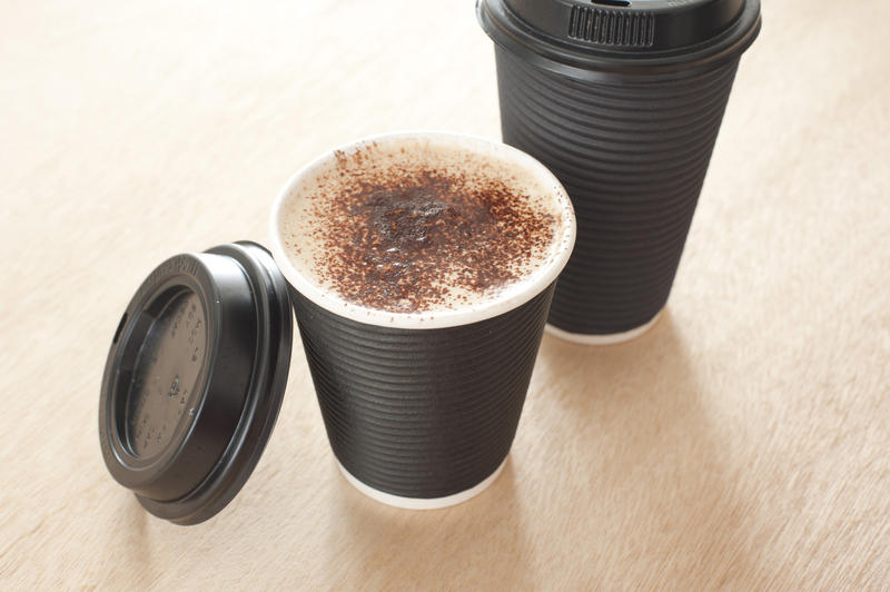Hot frothy takeaway coffee in a disposable cup with the lid off to display the beverage, high angle view