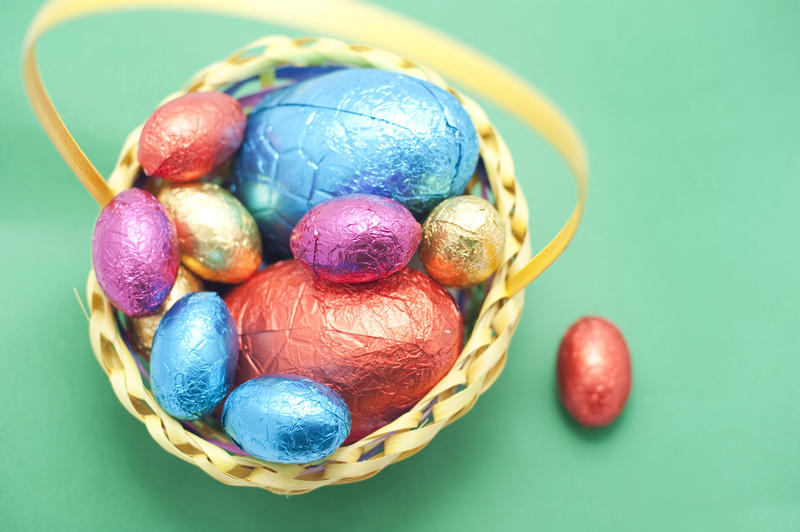 Overhead view of chocolate Easter Eggs in colourful foil wrappings in a basket on a green background
