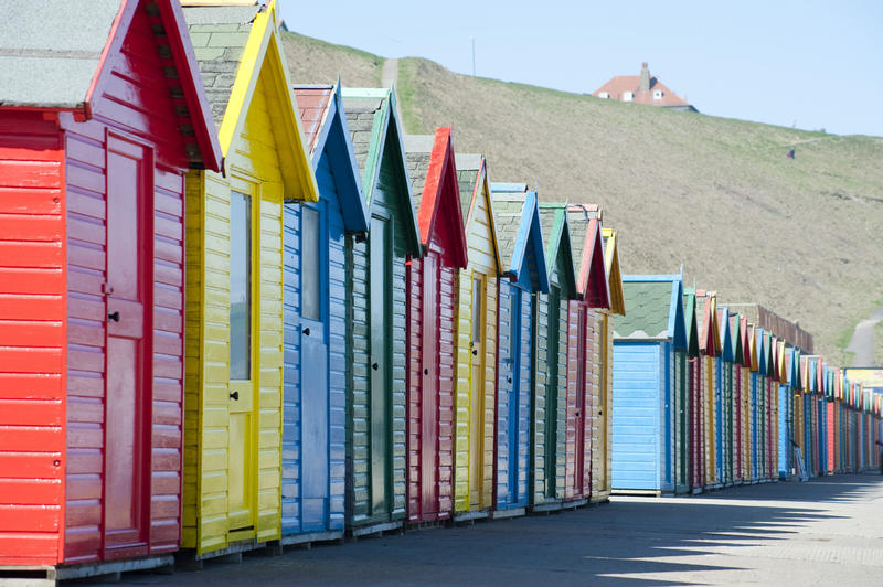 Row of colourful wooden Beach huts at Whitby sands on the West cliff or headland