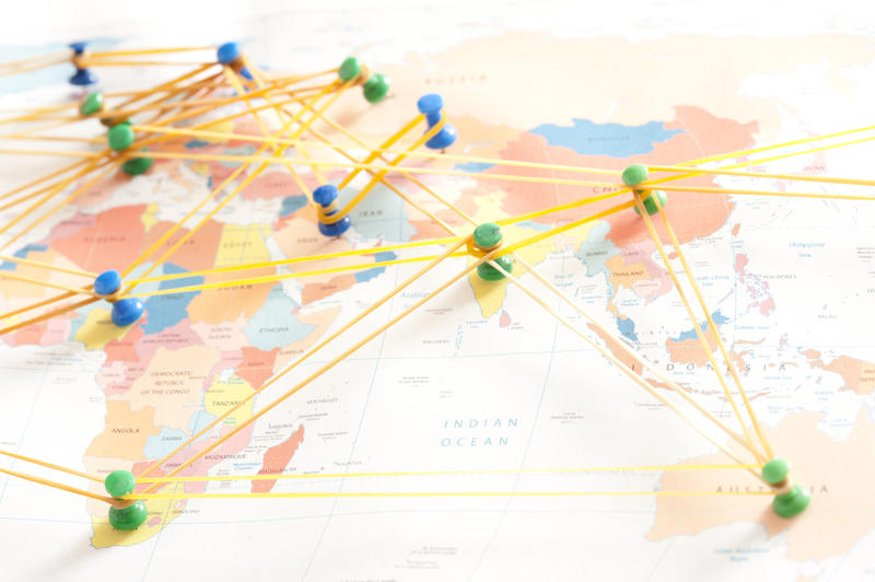 International network concept with colorful drawing pins or thumb tacks on a global map connected by rubber bands