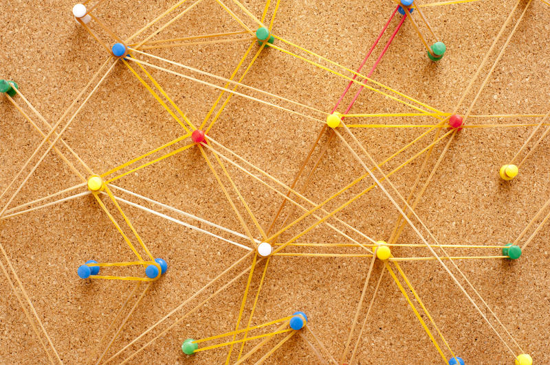 Networking Concept Using Colored Pins on Brown Cork Board Connected with Yellow Rubber Bands
