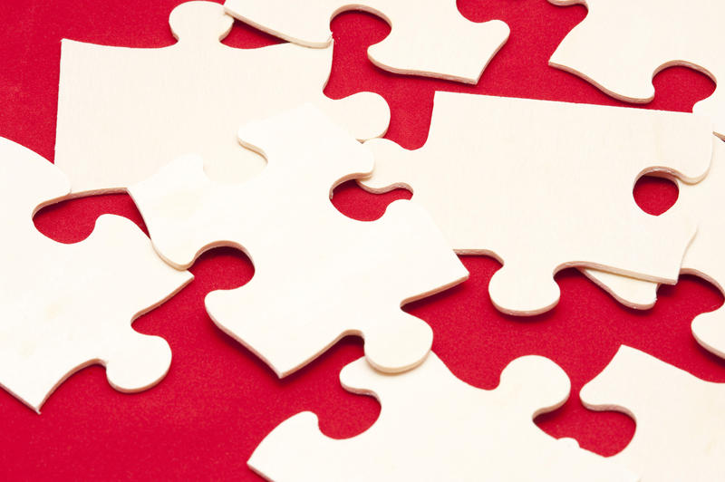 Scattered white jigsaw puzzle pieces on a colorful red background in a concept of problem solving