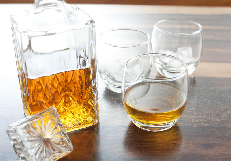 A glass liqour decanter with whiskey or similar inside and a glass