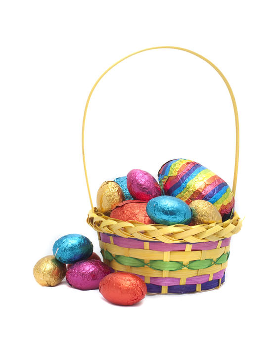 A decorative basket filled to overflowing with colourful foil wrapped Easter Eggs on a white background
