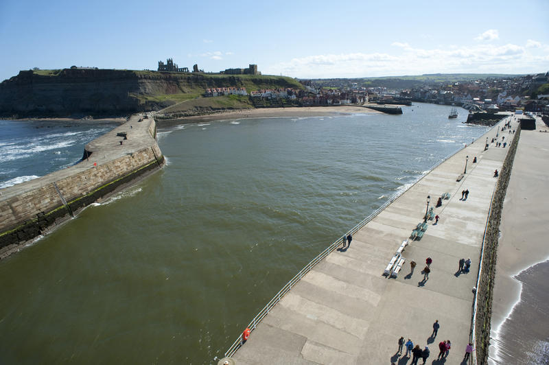 Aerial view of the Whitby piers looking back towards the town with people enjoying a walk along the promenade on top in the sunshine