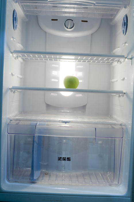 fridge empty but for a lone apple, concept of out of food, nothing to eat of a crash diet