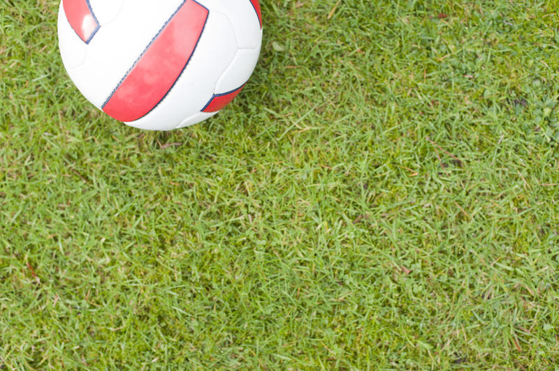 Football or soccer ball on neat manicured green grass with the red English colors on white, high angle view with plenty of copyspace