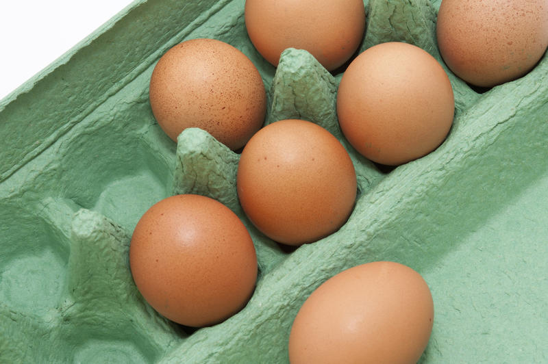 Close up Seven Fresh Brown Chicken Eggs on a Light Green Cardboard Tray
