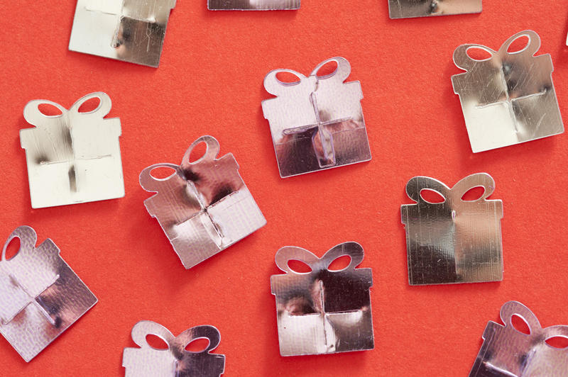 concept image of a party gift shower with silver coloured presents on a red background for good luck