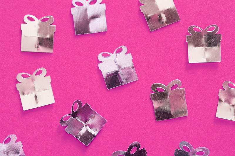 a feminine party gift background white metallic shapes on vibrant pink backdrop