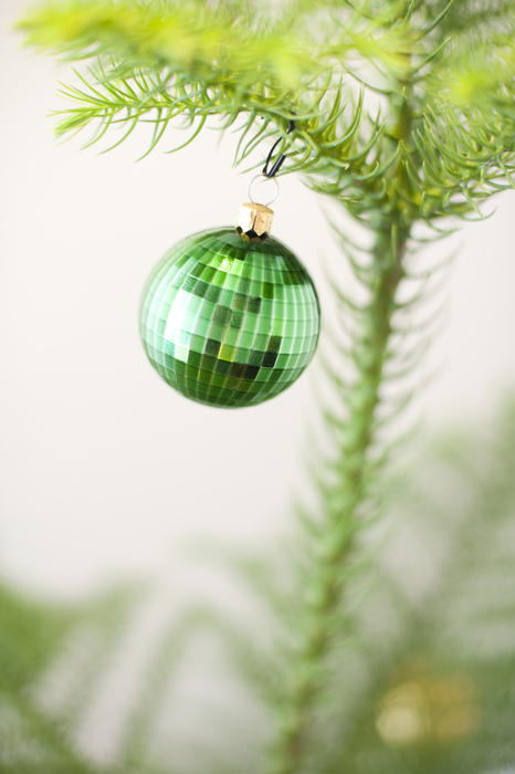 Green Christmas bauble hanging on a natural pine tree decorated to celebrate the Xmas season, close up with copyspace