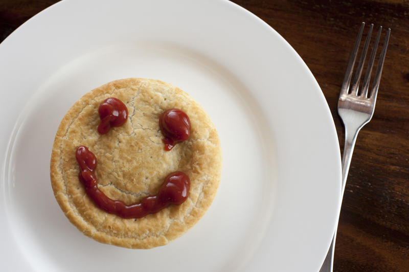 Happy meat pie with a smiley face formed of rich brown gravy on top of the pastry crust, overhead view on a plate