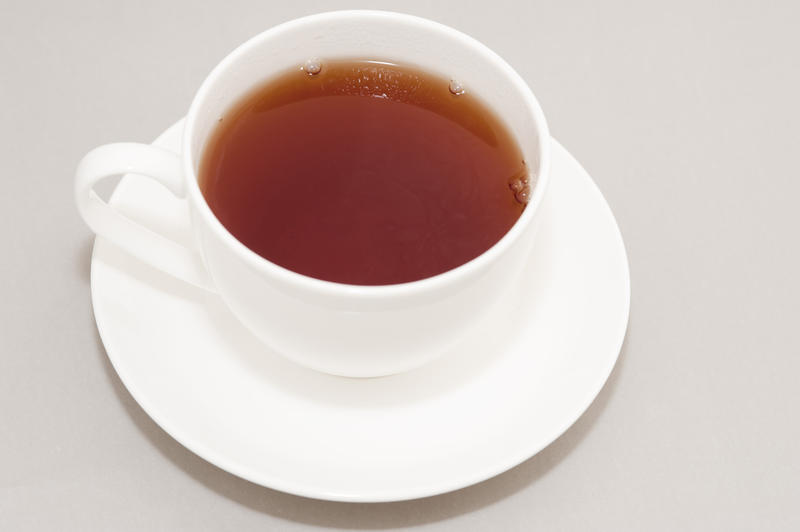 High Angle View of Hot Brewed Black Tea in Clean White Cup on Saucer in Studio with Neutral Gray Background