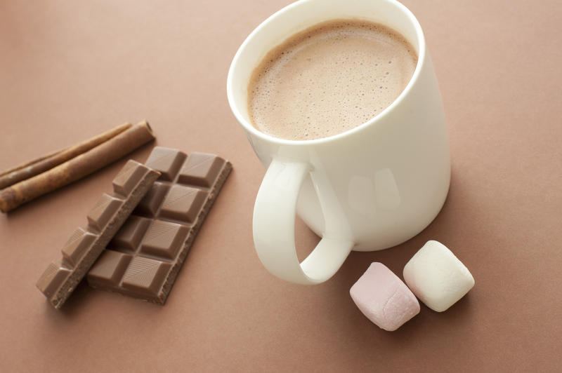 Hot chocolate drink with ingredients including marshmallows, stick cinnamon and a candy chocolate bar for a delicious winter beverage, high angle view