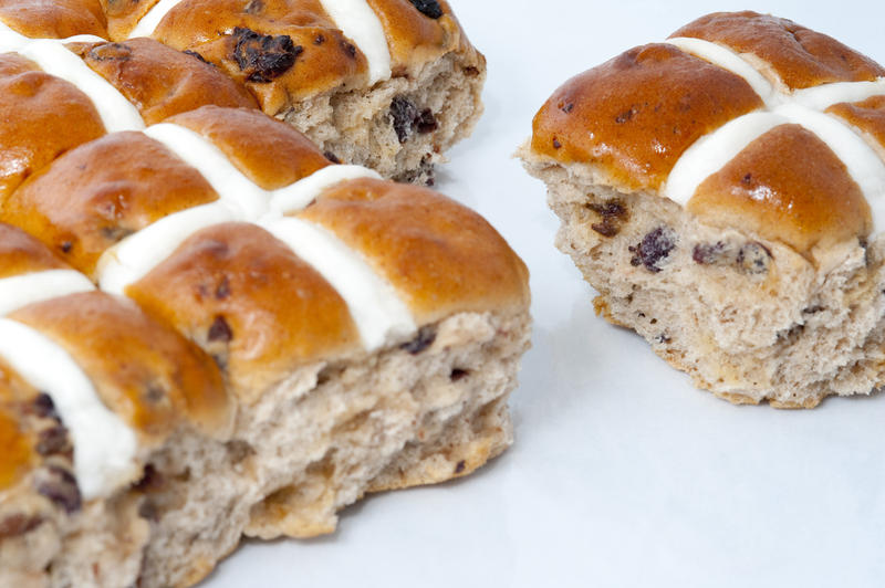 Freshly baked spicy Easter hot cross buns with glazed white pastry crosses on a white background