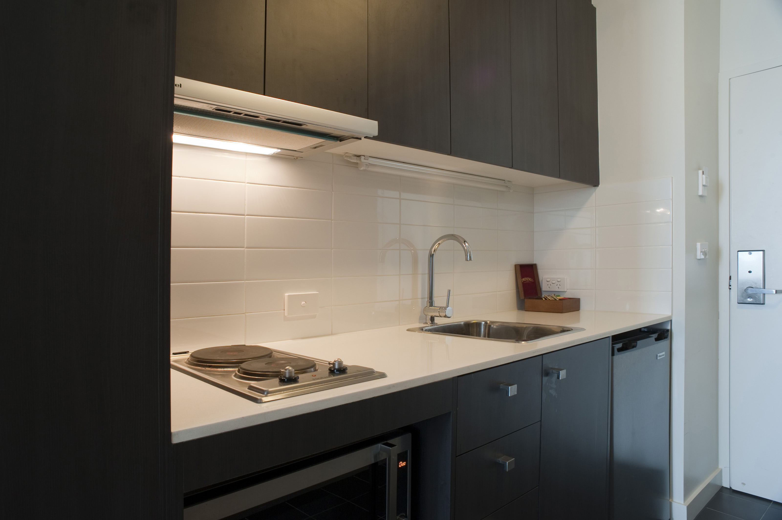 Interior of a modern compact kitchen with black cabinetry and a white tiled  splashback above a