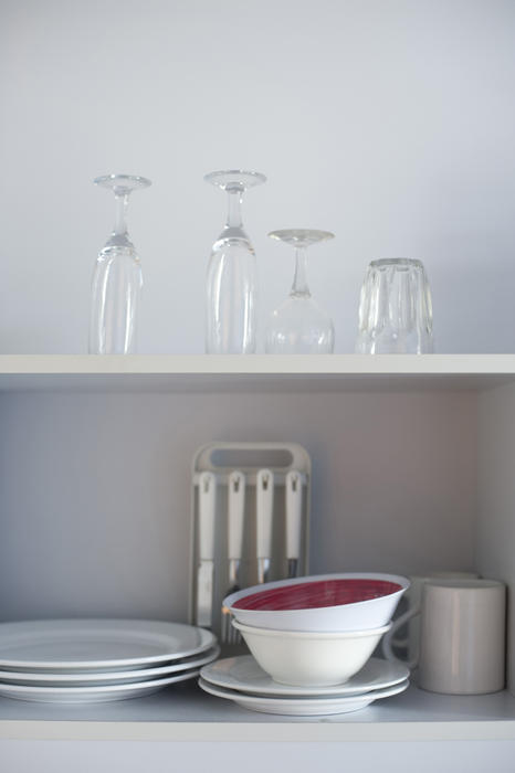 Open kitchen shelves stacked neatly with stored crockery, cutlery and glassware