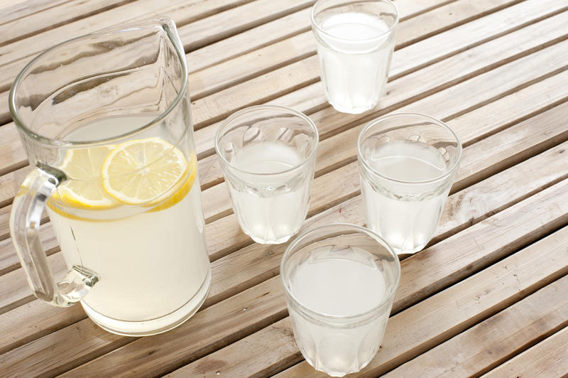 Delicious refreshing homemade lemonade with slices of fresh lemon served in a glass jug and tumblers on a wooden slatted picnic table in summer