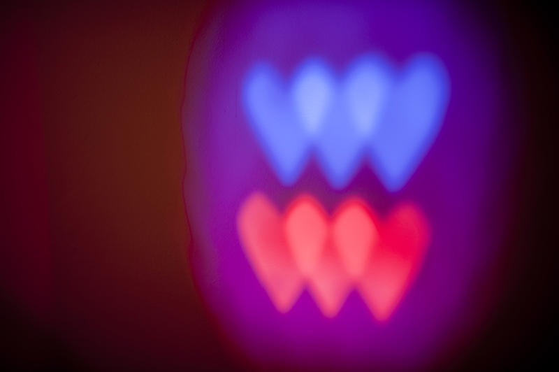red and blue colourd heart shapes painted with light on a dark background